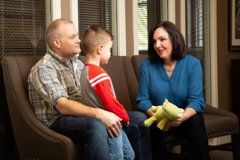 Personal Injury Attorney, Cyndi Crocker, talks with a male client and his son after a car accident