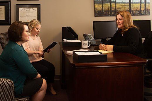 Personal Injury Attorney Robin Hewitt from Crocker Law Firm talks with two female case managers in her office