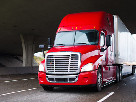 A red semi-truck is on the interstate traveling under a bridge