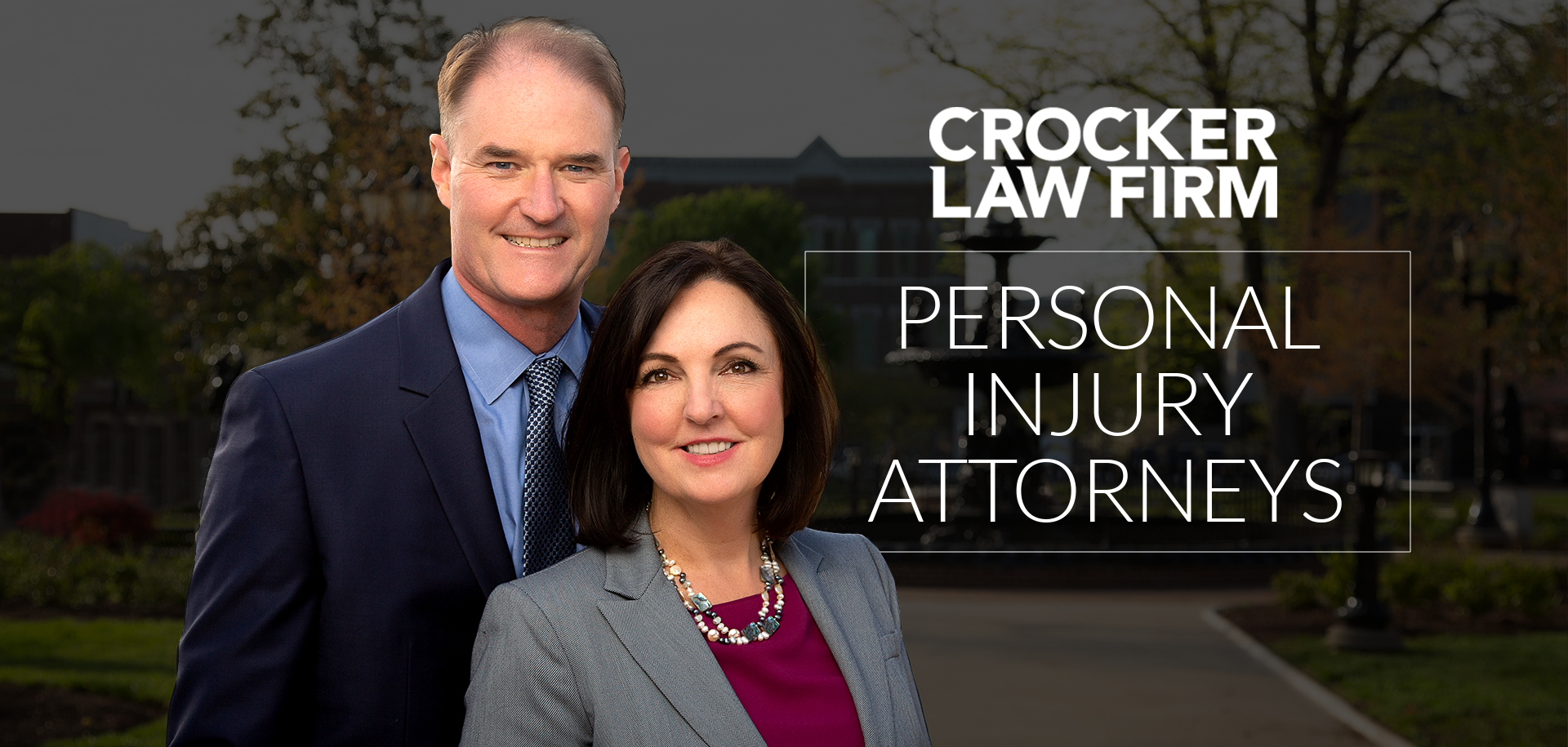Ben and Cyndi Crocker Partner Attorneys at Crocker Law Firm Personal Injury Attorneys smile at fountain square park with 'Personal Injury Attorneys' text