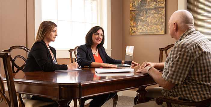 Cyndi Crocker Attorney at Crocker Law Firm and Andrea Hood Office Manager talk to a client in the conference room at Crocker Law Firm Personal Injury Attorneys in Bowling Green