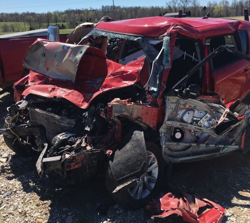 Beth Waddell's wrecked red Kia Soul car at a scrap yard with the front end smashed