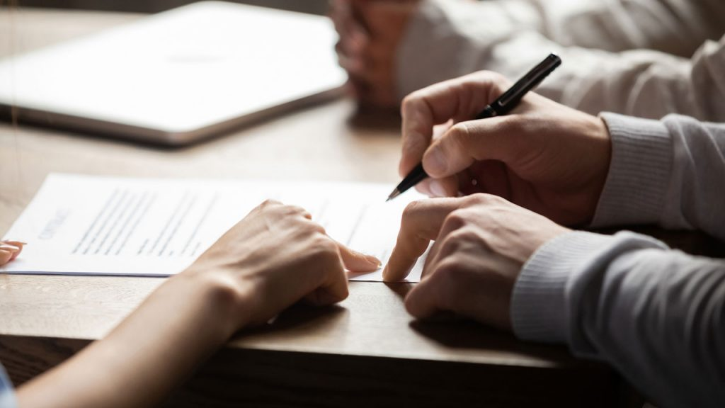 Hands are scene writing on a personal injury law contract in a board room.