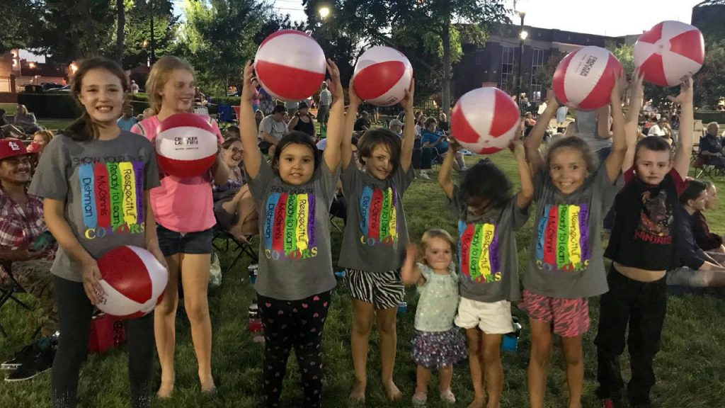 Kids at Bowling Green's Concerts in the Park hold up Crocker Law Firm Injury Attorney beach balls over their head