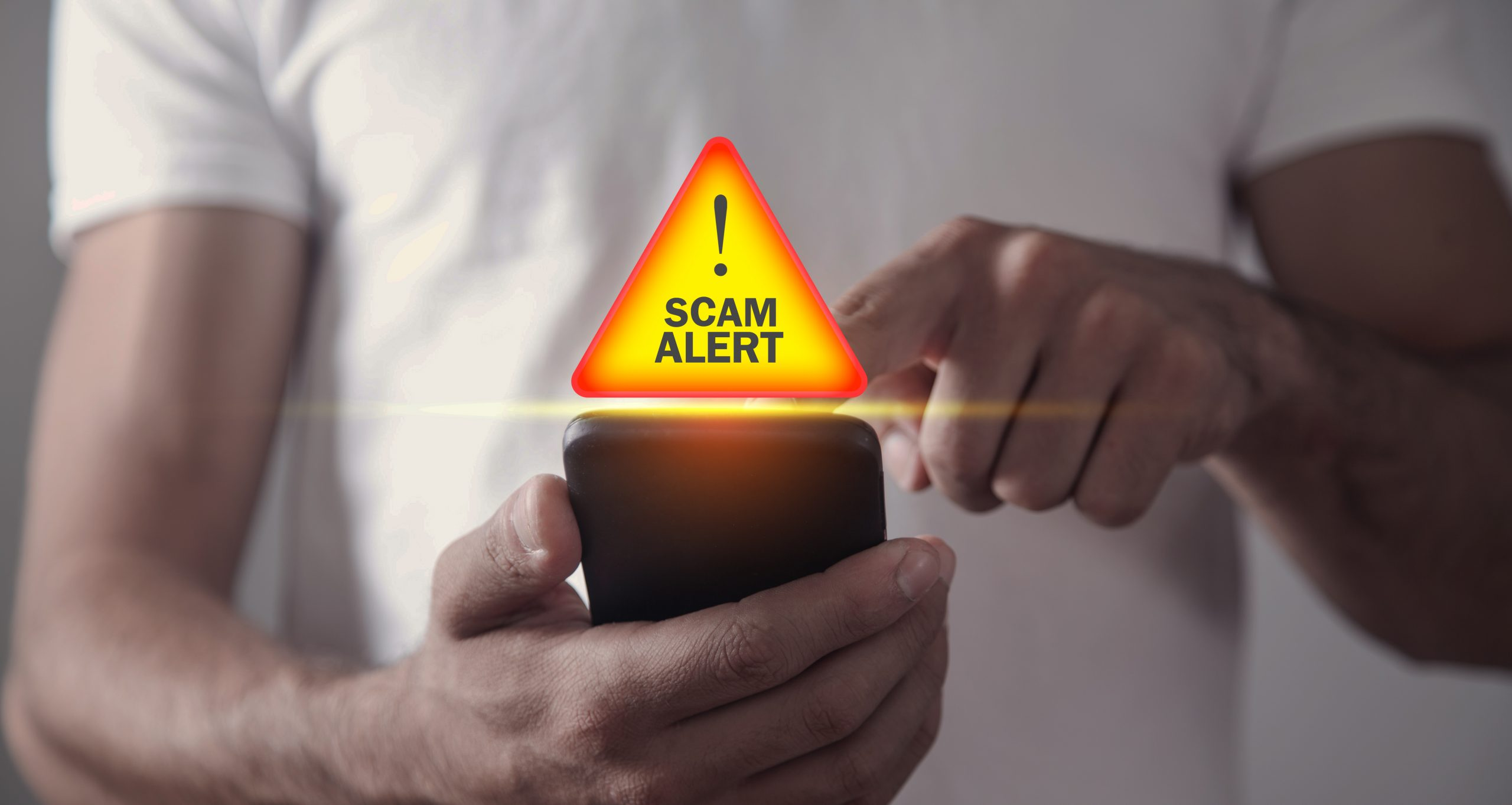 White man holding a cell phone with an illustration of a scam alert badge. Many online scams offer users a fake cash reward.