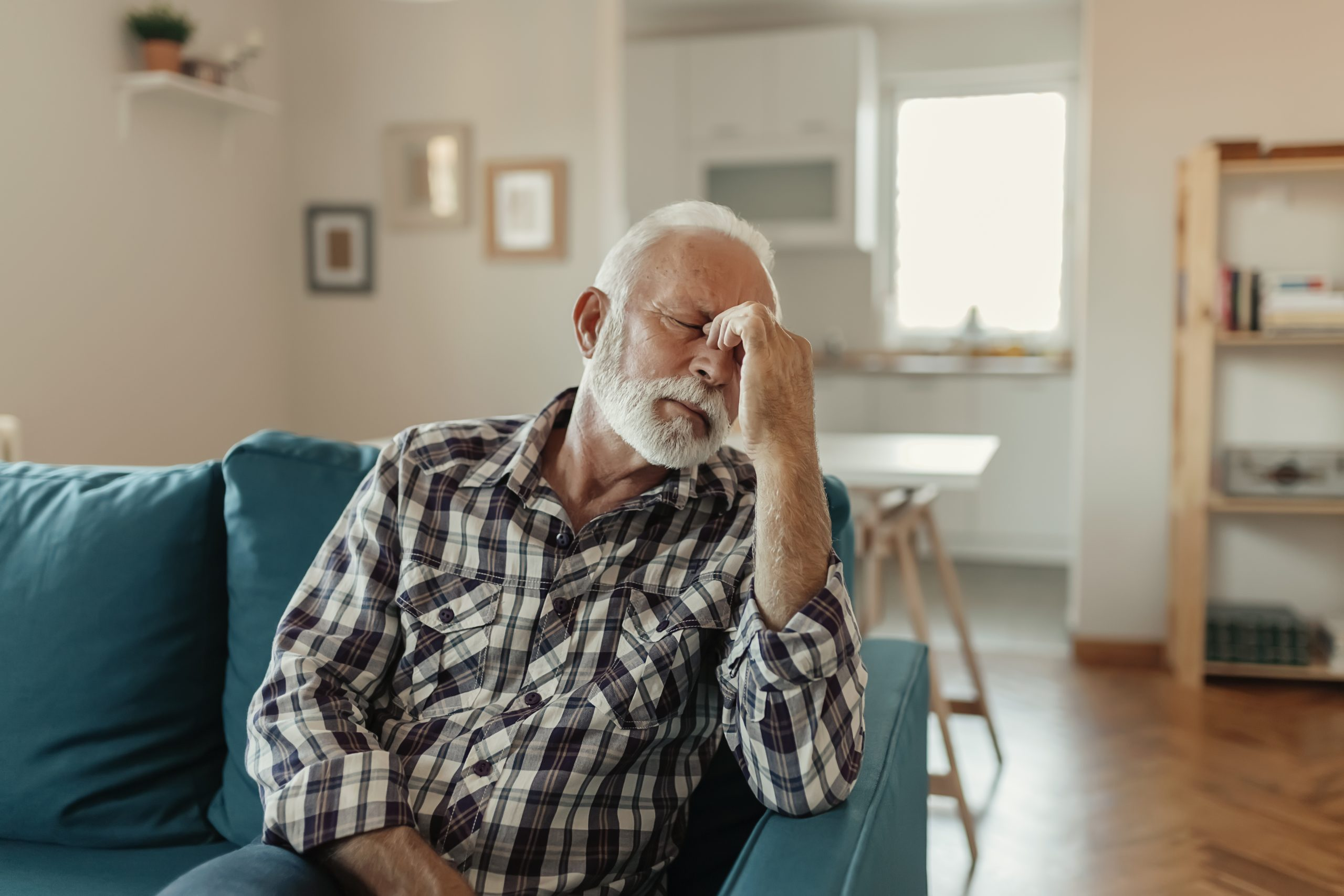 White man with a gray beard sitting on a couch, pinching the bridge of his nose and appearing in pain. Car accident injury symptoms are sometimes subtle.